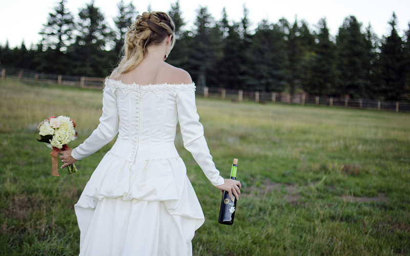 Wedding Wines for Under $10 - Bride with bottle of wine in a field