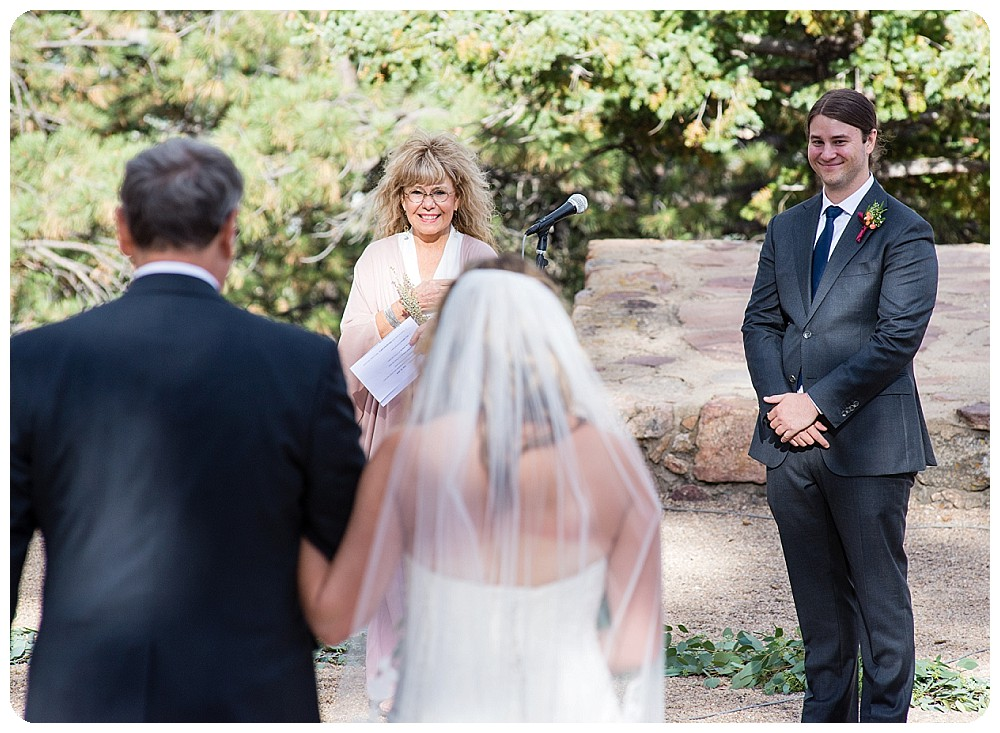 Grooms face with bride walkign down the aisle