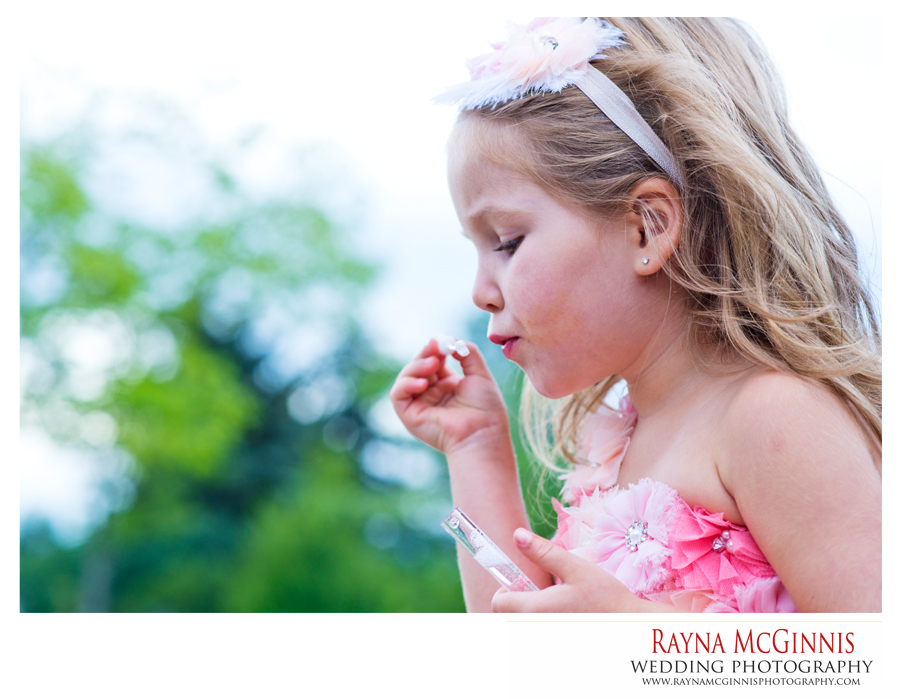 Flower girl blowing bubbles at hudson gardens wedding