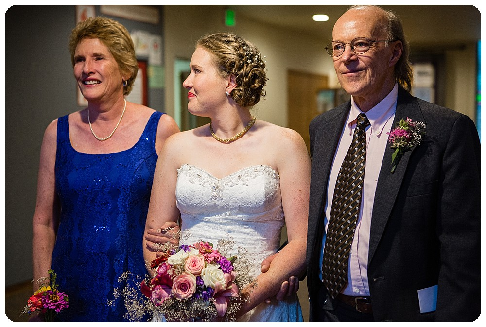 Bride about to walk down the aisle with both parents.
