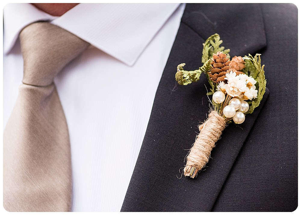 Groom tie and boutonniere in neutral colors