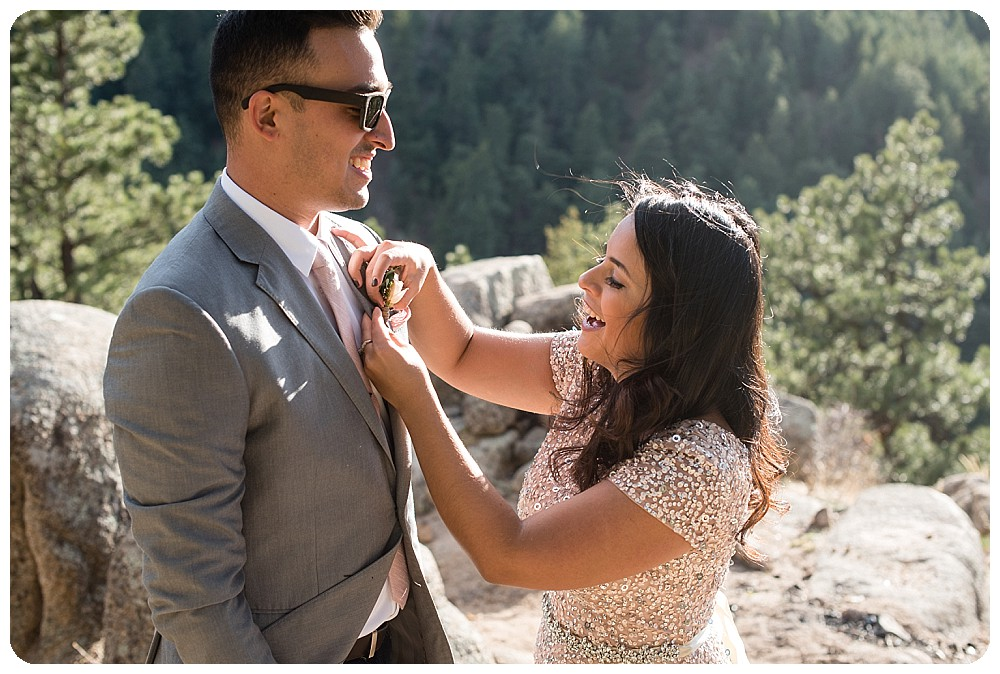 Bride pinning a boutonniere onto the groom at a Colorado Elopement