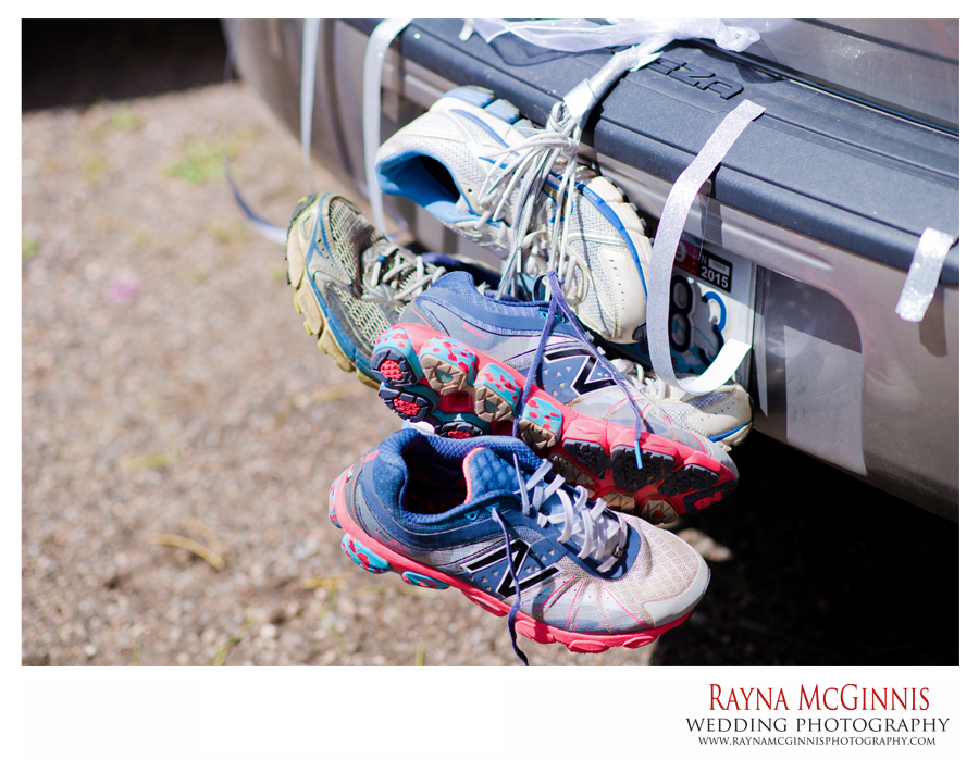 running shoes hanging off of bride and grooms car in colorado