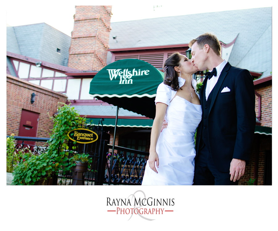 Bride and Groom kissing in front of the wellshire inn